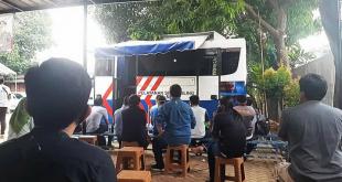 Warga tengah antre dengan menjaga jarak di layanan SIM keliling di Kampus Trilogi Kalibata, Jakarta Selatan
